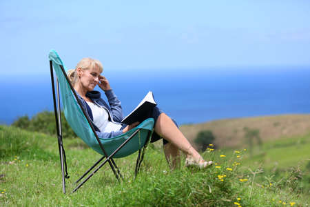 Senior woman reading book on hill by the sea photo