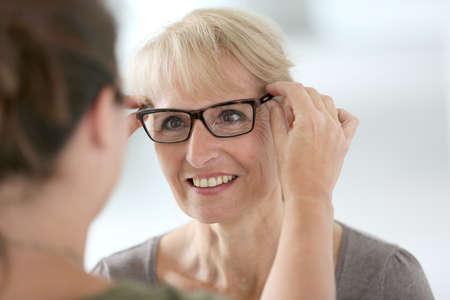 7d7eff1d7c64fe  30222179 - Hogere vrouw die nieuwe oogglazen in optische opslag probeert