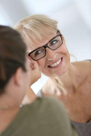 5db71453c7775d  30222342 - Hogere vrouw die nieuwe oogglazen in optische opslag probeert