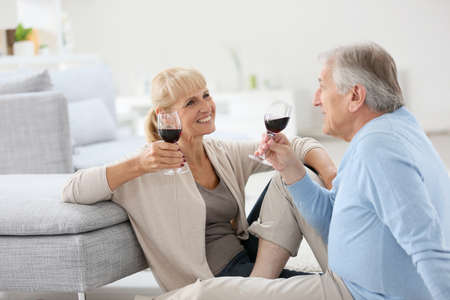 senior home: Senior couple at home drinking red wine