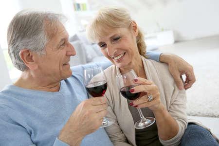 bebiendo vino: Senior pareja en casa bebiendo vino tinto