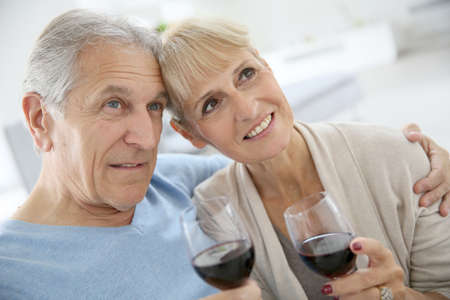 Senior couple at home drinking red wine photo