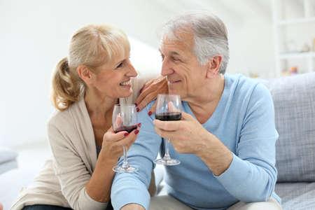Cheerful senior couple cheering with glass of wine photo
