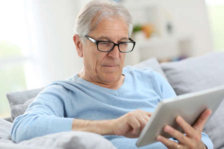 Senior man reading news on digital tablet  Stock Photo