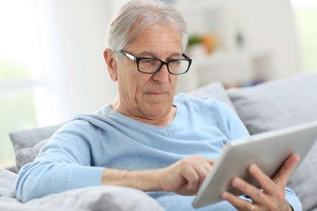 eye pad: Senior man reading news on digital tablet  Stock Photo