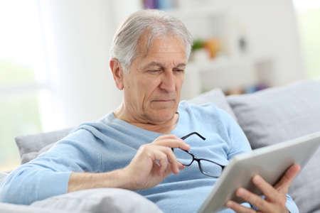 Senior man reading news on digital tablet  Фото со стока