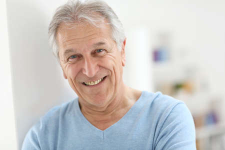 old man standing: Portrait of smiling senior man with blue shirt