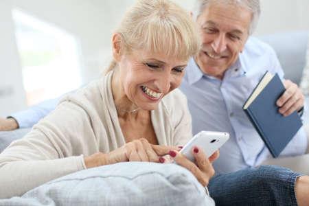 Senior woman using smartphone, husband reading book photo