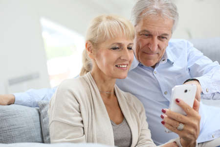 Senior couple at home using smartphone Stock Photo