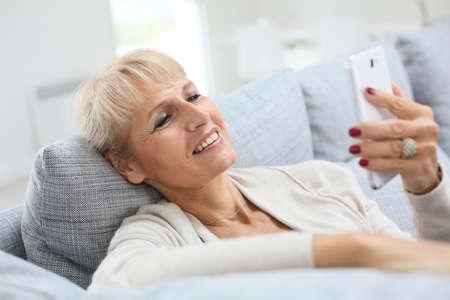 Senior woman reading message on smartphone photo