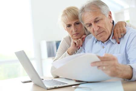 renta: Pares mayores que hacen la declaraci�n de la renta en l�nea Foto de archivo
