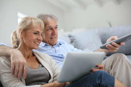 tv: Senior couple assis dans un canapé et regarder la télévision Banque d'images