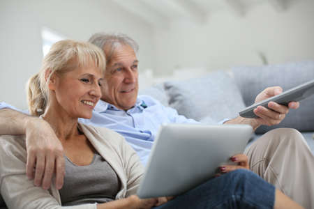 sofa television: Senior couple sitting in sofa and watching tv