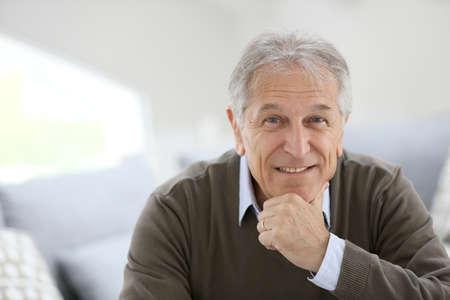 自宅のソファーに座っている笑顔の年配の男性の肖像画 写真素材