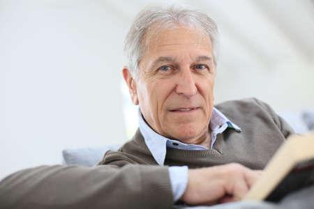 Senior man reading book relaxed in sofa Imagens