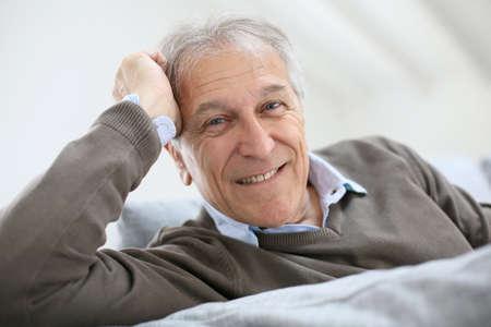 Portrait of smiling senior man sitting on sofa at home