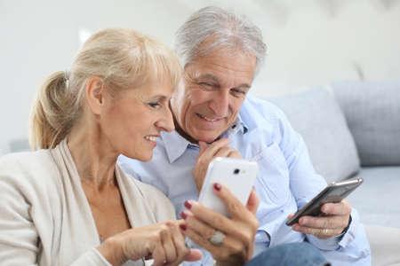 Senior couple at home using smartphone Stockfoto