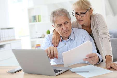 所得税の確定申告をオンラインを行うシニア カップル 写真素材
