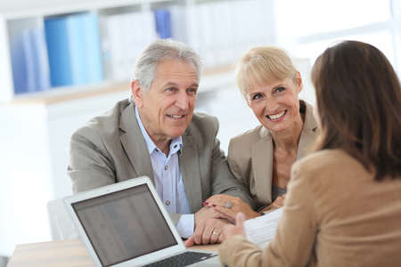 Senior couple meeting financial adviser in office photo