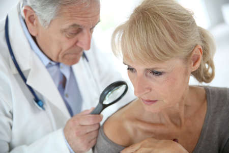 beauty spot: Doctor using magnifying glass to check on beauty spot Stock Photo