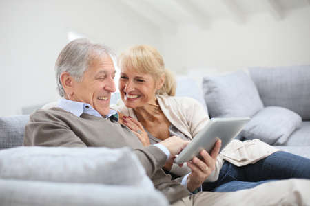 websurfing: Cheerful senior people websurfing on internet with tablet Stock Photo
