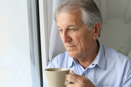 old man standing: Senior man looking by window, holding cup of tea