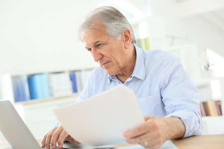 taxation: Senior man working on laptop computer
