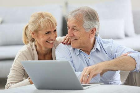 websurfing: Senior couple websurfing on internet with laptop