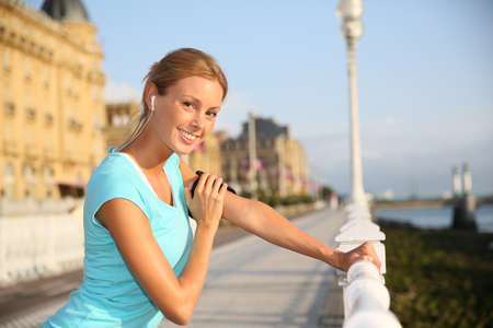 handrail: Woman in town stretching out after running