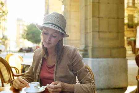 expresso: Young woman in the city sitting at coffee shop