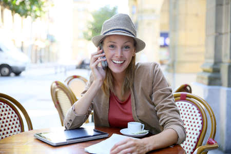 Cheerful modern girl in coffee shop talking on phone photo