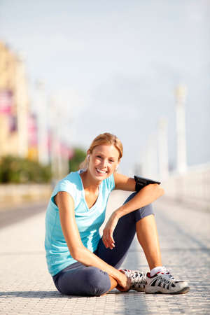 Cheerful jogger stretching after exercising in the\ street