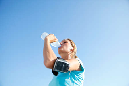 Jogger woman drinking water from bottle photo