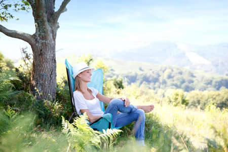 folding chair: Young woman enjoying peaceful time in countryside