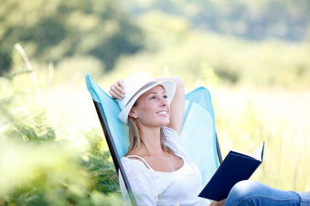 folding chair: young woman reading book in outdoor chair Stock Photo