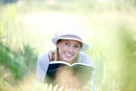 Smiling woman laying in grass and reading book photo