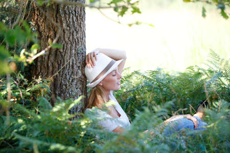 Young woman with hat relaxing in forest photo