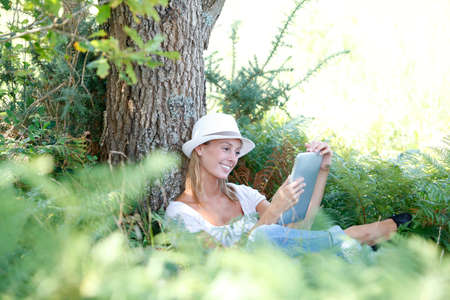 novel: Woman in countryside reading novel on tablet Stock Photo