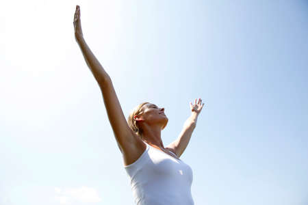 Woman doing relaxation exercising, stretching arms up photo