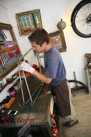 Man in bicycle shop fixing bike frame photo