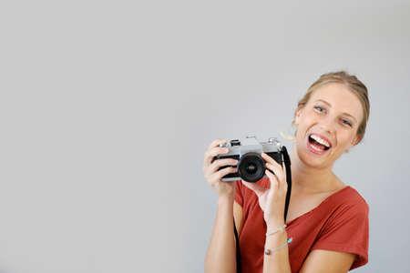 amateur: Muchacha alegre con la cámara de la vendimia sobre fondo gris Foto de archivo