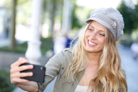 selfy: Trendy girl with hat taking picture with smartphone Stock Photo