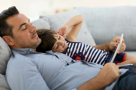 single parent: Daddy with little girl playing with tablet