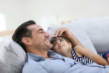 single father: Daddy with little girl relaxing in sofa Stock Photo