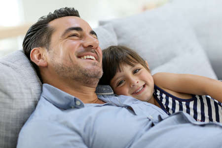 Daddy with little girl relaxing in sofa Stock Photo