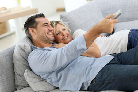 woman on couch: Middle-aged couple in sofa watching tv