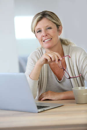 Middle-aged woman working on laptop at home Stock Photo