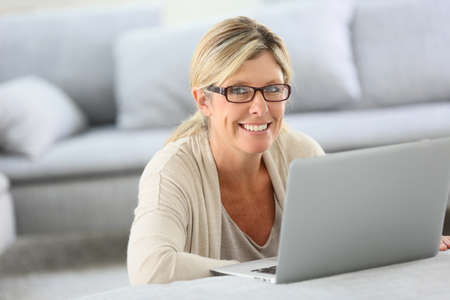 websurfing: Mature woman with eyeglasses websurfing on laptop