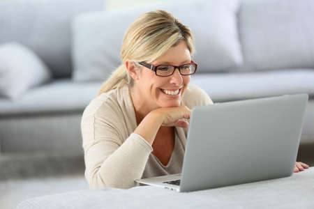 mature woman: Mature woman with eyeglasses websurfing on laptop