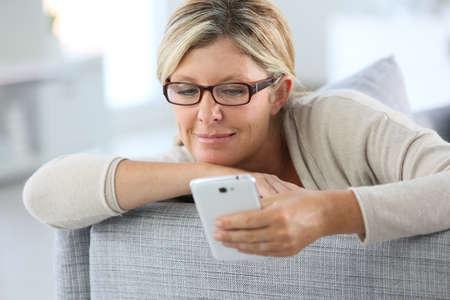Blonde vrouw lezen van tekst bericht op de smartphone